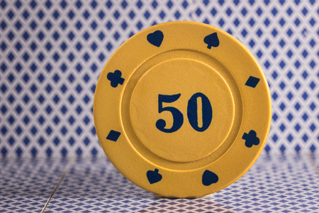 yellow poker chip closeup on the back of playing cards concept of the most popular and gambling card game in the world Stock Photo