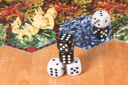 Light and dark dice on the surface of a wooden table in the background of a playing field and plastic monsters