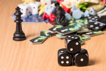 three dark dice on a blurred background of chess pieces domino chips concept of passive and popular recreation