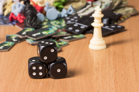 popular objects for board games and a small pyramid of dark dice The concept of logical games and passive recreation