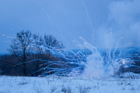 blurry evening background the explosion of a combat projectile over a snow covered field of a spark beautifully scattered in different directions