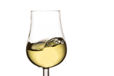 magnificent white wine splashing in a glass on a white background a delicious alcoholic drink made from grapes