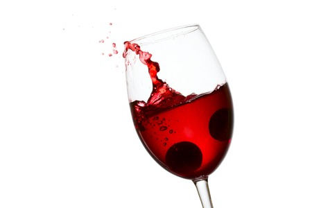 spectacular splash and flying drops of red wine in an elegant glass with fallen grapes on a white background concept of a popular alcoholic beverage