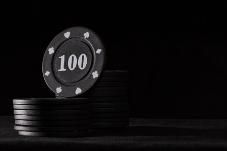 black chips for poker games are brightly highlighted on a dark background the concept of business and gambling