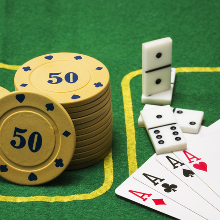 chips for poker dominoes and four aces on the green canvas concept of popular board games