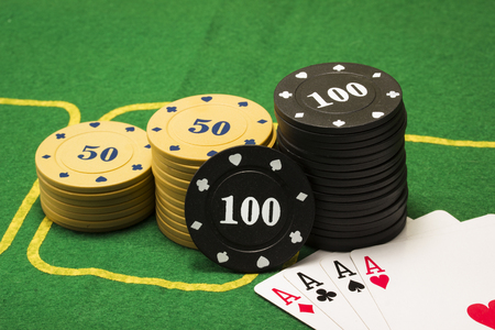 multicolored poker chips and a card combination four aces on a green canvas concept of gambling and casino Stock Photo