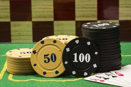 columns of poker chips and a combination of four aces on a chess board background concept of gambling and casino