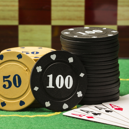 round poker chips and playing cards on a chessboard background objects for popular board games