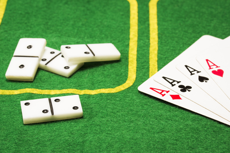 Domino and a combination of four aces on a green canvas The concept of popular board games