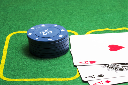 column of blue poker chips and three aces on a green canvas concept of casino and gambling Stock Photo