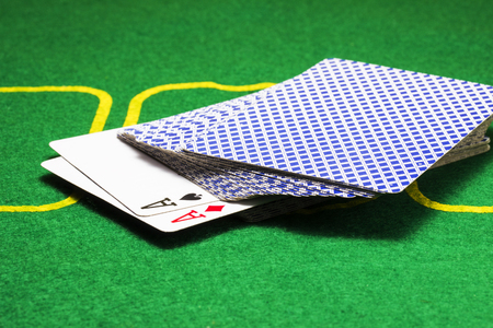 two aces peeking out of a deck of cards on a bright green canvas concept of board games and casino Stock Photo