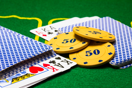 bright objects for playing poker chips and playing cards on the green canvas concept of board games and casinos