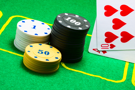 poker chips and fallen on the edge of playing cards concept of popular gambling around the world Stock Photo
