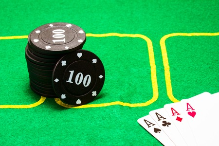 column of black poker chips and a combination of four aces on a green canvas concept of casino and board games