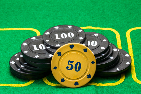 bright orange poker chip leaned against the black against the backdrop of a bright green canvas concept of gambling and casino