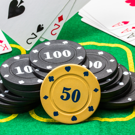 poker chips against the background of falling and lying on the green canvas playing cards concept of business and casino