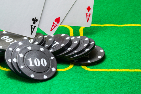 black poker chips on which three aces fall on a bright green canvas concept of board games and casino