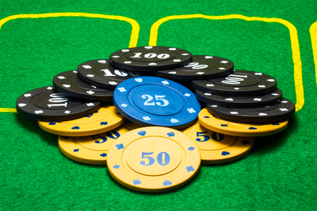 Poker chips are lined in the shape of a diamond on a bright green canvas The concept of casino and table games