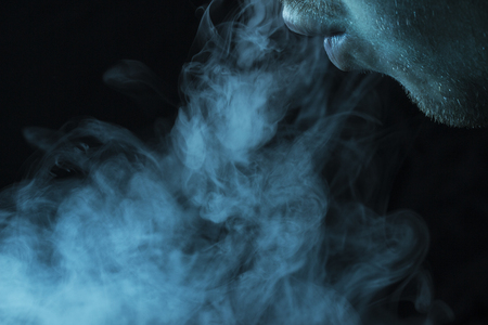 cloud of cigarette smoke comes from the mouth on a dark background The concept of smoking and nicotine addiction