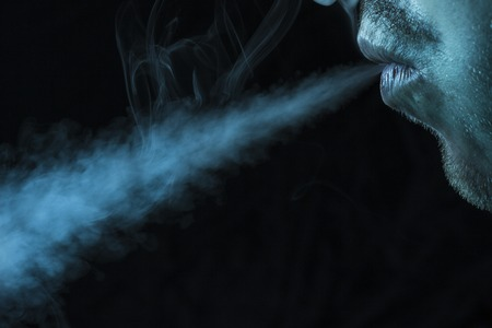 guy lets out a jet of cigarette smoke on a dark background concept of smoking and bad habits