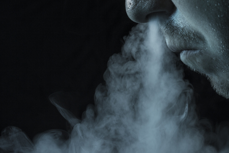 cigarette smoke flies out of the nose of a man close up on a dark background concept of fighting smoking 版權商用圖片