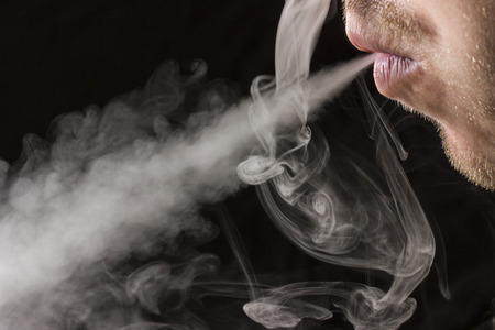 man mouth exhales a stream of cigarette smoke on a dark background concept of smoking and social problems