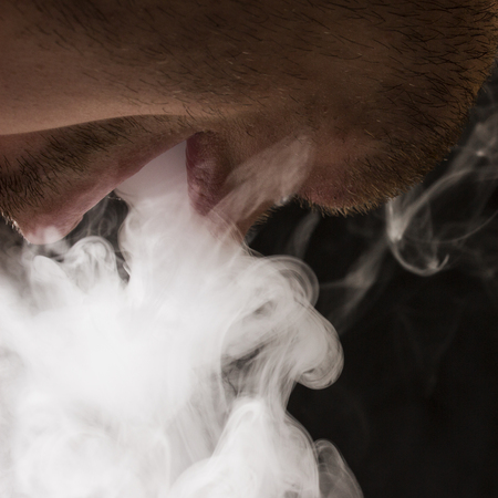 the smoker opened his mouth and lets out a cloud of cigarette smoke on a dark background the concept of smoking and relaxing