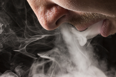 gray cigarette smoke comes from an open mouth of a smoker on a dark background a concept of pleasure and relaxation