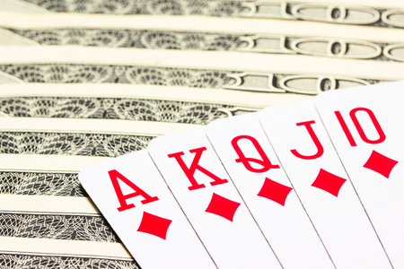 diamond royal flush on dollar bills closeup concept of winnings and business