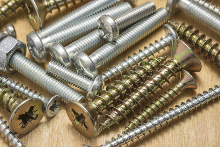 bright bolts and screws on a wooden background closeup concept of tools and repair Reklamní fotografie - 113610584