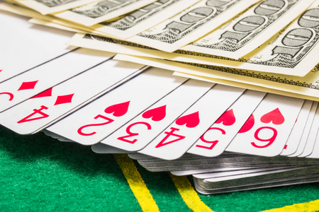 deck of playing cards under a fan of dollar bills on a green canvas for playing poker The concept of winning and casino Foto de archivo