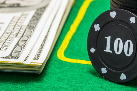 column of poker chips and a lot of dollar bills on a green canvas concept of winning and casino Stock Photo