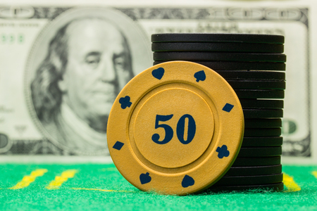 column of poker chips on a blurred background of a dollar bill concept of winning and casino Stock Photo