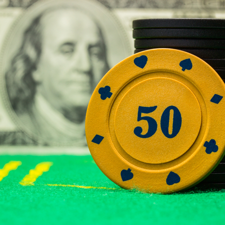 bright orange poker chip on a blurred background of dollar bill closeup concept of casino and gambling