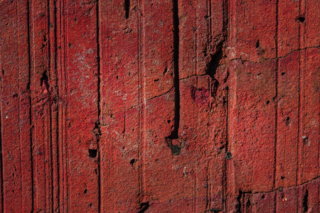 texture of red brick with cracks and potholes close-up stone background for design concept of building materials