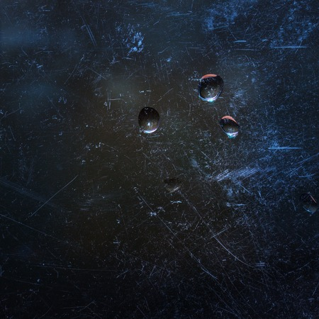 fantastic abstraction of a drop of water on a scratched glass behind which the night sky background for design a mysterious atmosphere Standard-Bild