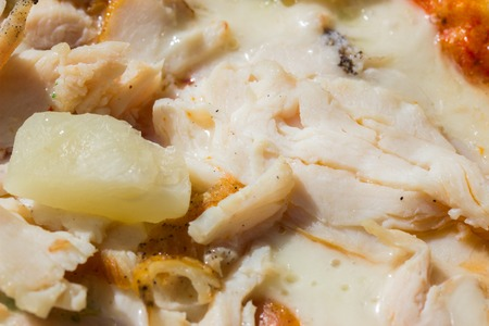 appetizing surface of a pizza with chicken and pieces of pineapple close-up concept of eating