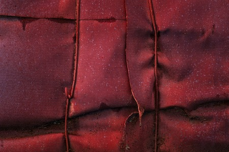red and mysterious fiberglass texture covering a metal pipe dirty and not smooth surface grunge background for design