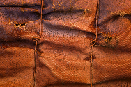 brown texture of old rumpled fiberglass with cracks on the surface and with metal wire industrial background for design