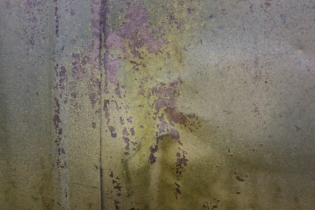 not smooth surface of metal construction covered with multicolored, partially peeled off old paint background for design