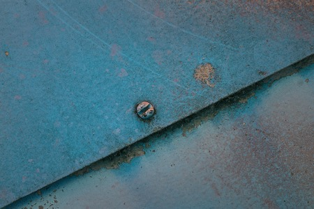 bright blue texture of metal sheets butt fastened with a screw diagonally the background for design