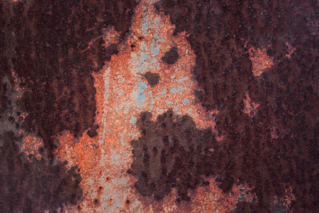 dark texture of a sheet of rusty metal with an interesting pattern of peeling paint close-up industrial background for design
