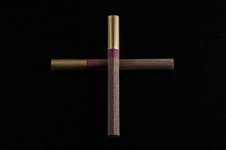 cross laid out of two cigarettes on a dark background the concept of death from bad habits