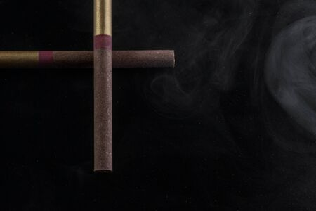 two cigarettes and a cloud of vapor on a dark background the concept of unhealthy habits and slavery
