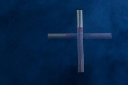 cross laid out of two cigarettes lies in blue smoke mysterious atmosphere concept of addiction