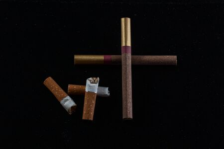 cross laid out of cigarettes and cigarette butts lie next to on a dark background the concept of smoking and bad habits Stok Fotoğraf