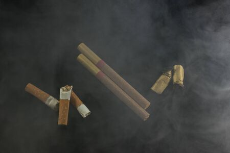 two solid cigarettes lie in the smoke with crumpled disgusting cigarette butts the concept of combating smoking and bad habits