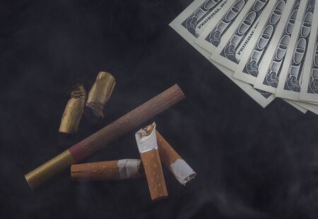cigarette butts and hundred-dollar American bills lie in the smoke on a dark background the concept of the cost of smoking and drugs