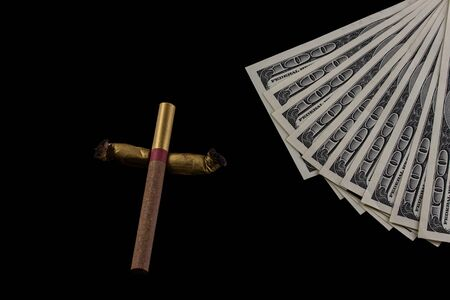 cross made of cigarettes and cigarette butts a fan of one hundred dollar bills on a black background the concept of the cost of bad habits Stock Photo
