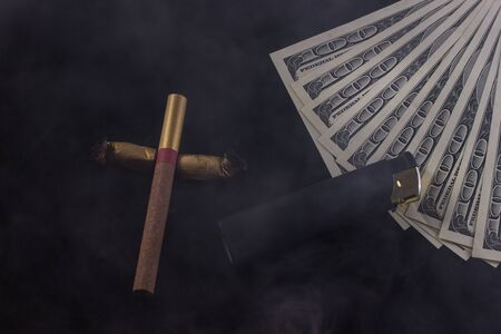 cross made of cigarettes and cigarette butts a lighter and one hundred dollar bills lie in the smoke on a dark background the concept of bad habit and drug costs